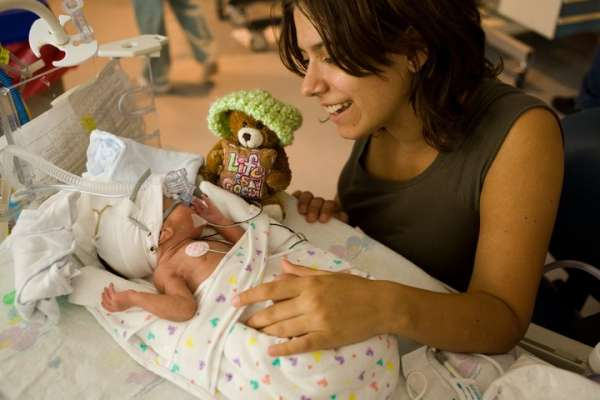 Woman showing a teddy bear to a baby in the hospital