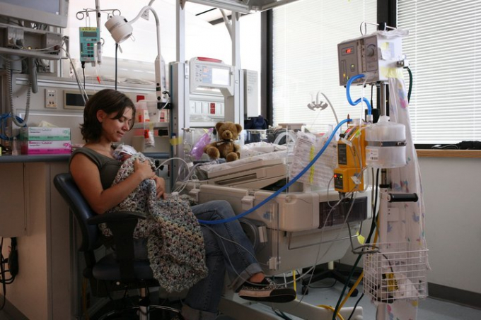 Woman sitting in the NICU holding baby